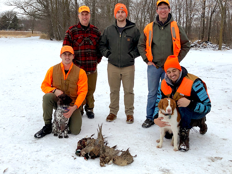 5 hunters with two dogs and pheasant hunting catch in winter